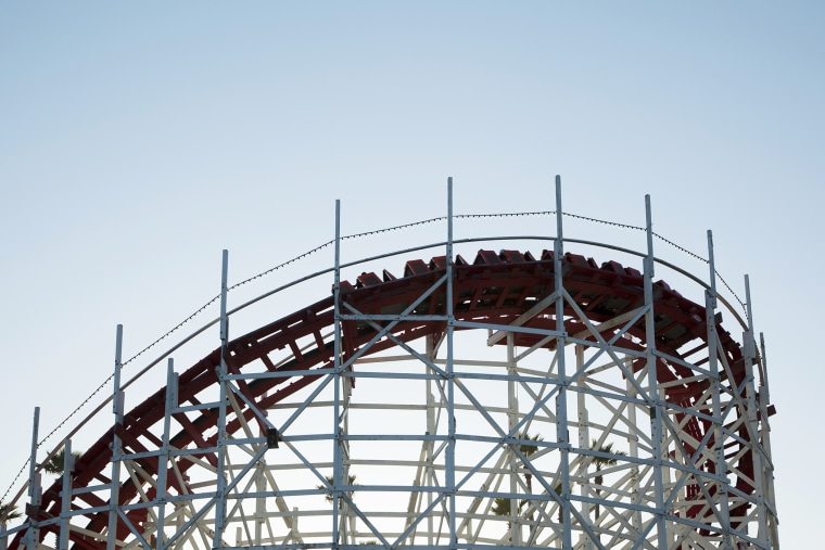Roller coaster cars turn on a curve. (Photo by Stephen Tamiesie/Gallery Stock)
