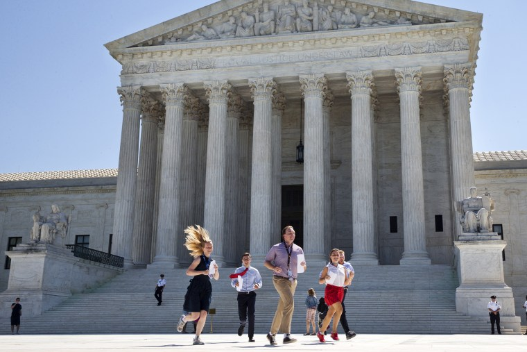 New interns run with a decision across the plaza of the Supreme Court in Washington, June 29, 2015. (Photo by Jacquelyn Martin/AP)