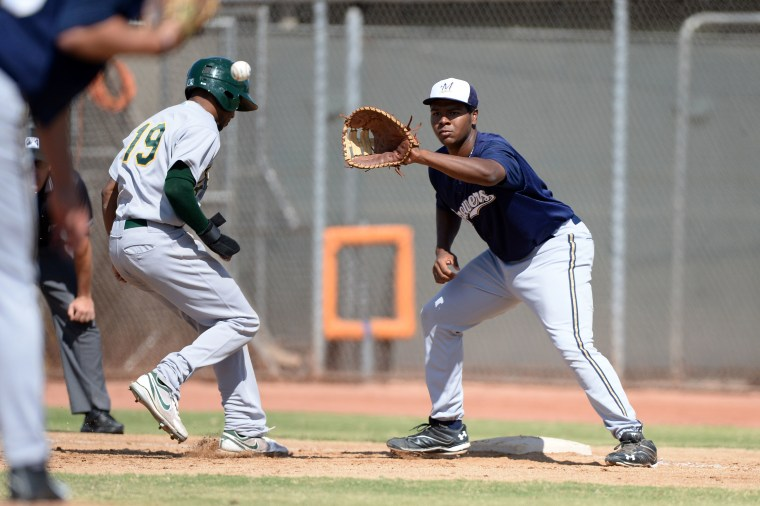 Milwaukee Brewers first baseman David Denson (8) takes a throw as D'Arby Myers (19) gets back to the bag during an Instructional League game against the Oakland Athletics, Oct. 10, 2013, Phoenix, Ariz. (Photo by Mike Janes/Four Seam Images/AP)