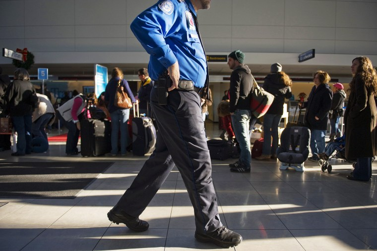 A Transportation Security Administration official walks by passengers at the Baltimore Washington International Airport. (Photo by Jim Watson/AFP/Getty)