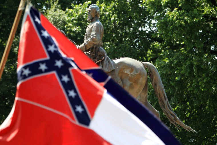 A Mississippi state flag waves in front of the statue and tomb of Nathan Bedford Forrest, rebel general, slave trader and early Ku Klux Klan member, during a celebration of Forrest's 194th birthday at Health Sciences Park in Memphis, Tenn.