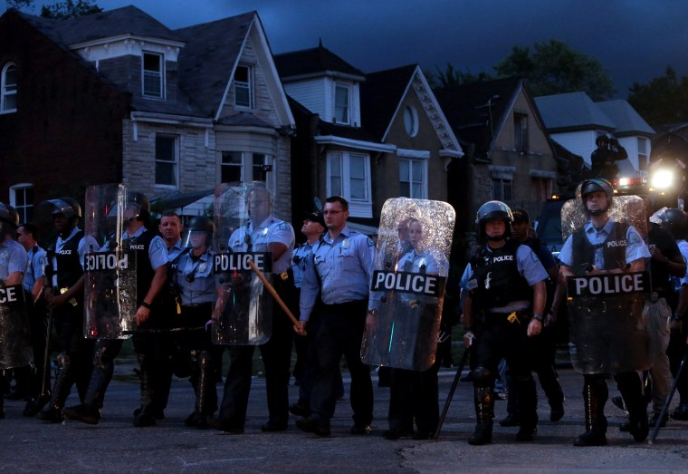 Police stand guard as protesters gather, Aug. 19, 2015, in St. Louis after a black 18-year-old fleeing from officers serving a search warrant was fatally shot after police say he pointed a gun at them. (Photo by Laurie Skrivan/St. Louis Post-Dispatch/AP)