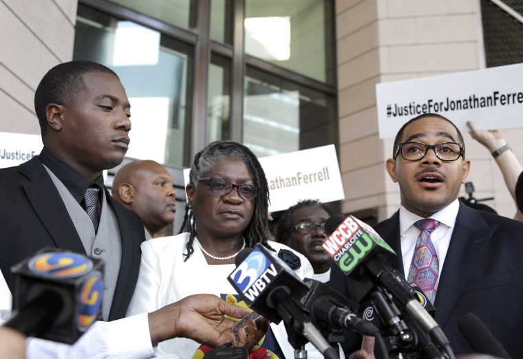 Willie and Georgia Ferrell listen as their attorney, Christopher Chestnut, talks with reporters about the mistrial in the case of Charlotte policeman Wes Kerrick accused of killing their brother and son, Jonathan, Aug. 21, 2015. (Photo by Bob Leverone/AP)