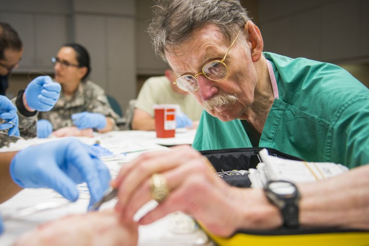"""Dr. James """"Red"""" Duke instructs a group of U.S. Army flight medics in suturing techniques using pigs feet at Memorial Hermann Hospital in Houston, Texas on Aug. 15, 2013. (Photo by Smiley N. Pool/Houston Chronicle/File/AP)"""