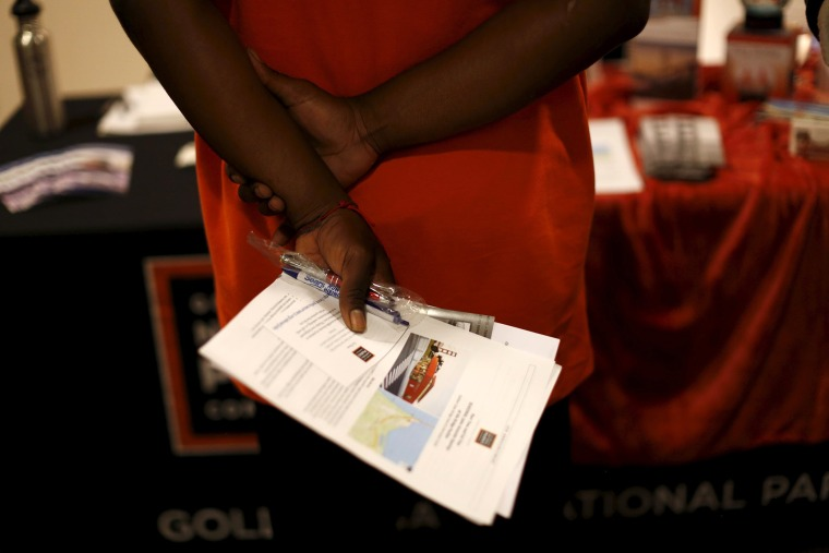 A job seeker holds literature while waiting to speak with a representative of the Golden Gate National Parks Conservancy at a career fair in San Francisco, Calif., July 14, 2015. (Photo by Robert Galbraith/Reuters)