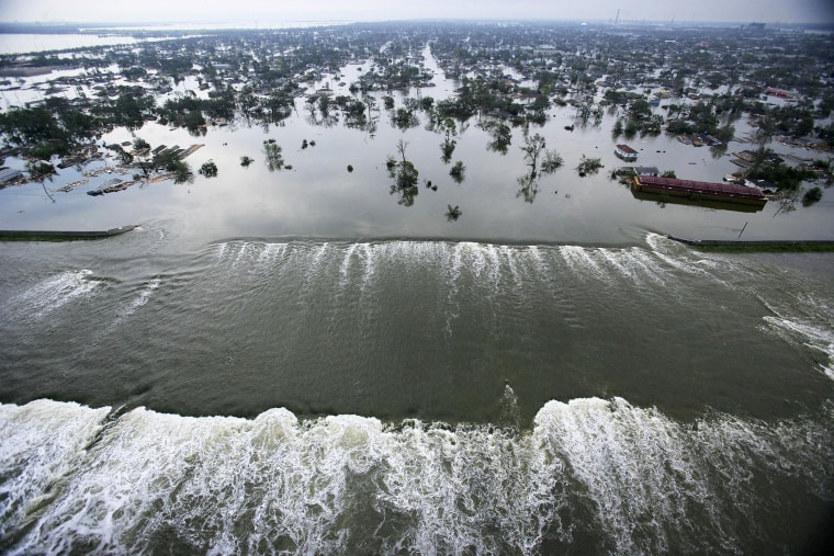 Water spills over a levee along the Inner Harbor Navigational Canal in the aftermath of Hurricane Katrina on Aug. 30, 2005 in New Orleans, La. (Photo by AFP/Getty)