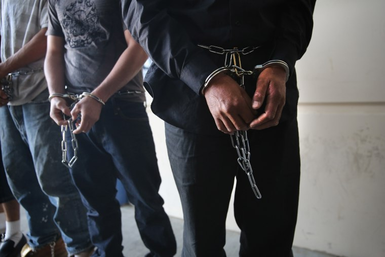 Immigrants prepare to be unshackled at a detention facility on Nov. 15, 2013 in California. (Photo by John Moore/Getty)