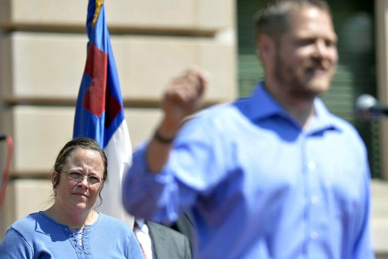 Rowan County Clerk Kim Davis, left, listens as Casey County Clerk Casey Davis speaks to a group of supporters during a rally at the Kentucky State Capitol in Frankfort Ky., Saturday, Aug. 22, 2015. (Photo by Timothy D. Easley/AP)
