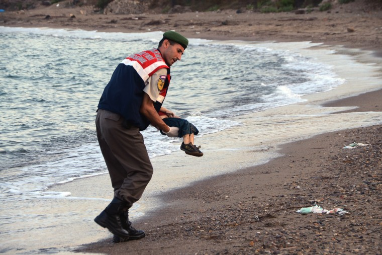 A paramilitary police officer carries the lifeless body of a migrant child near the Turkish resort of Bodrum early Wednesday, Sept. 2, 2015. (Photo by DHA/AP)
