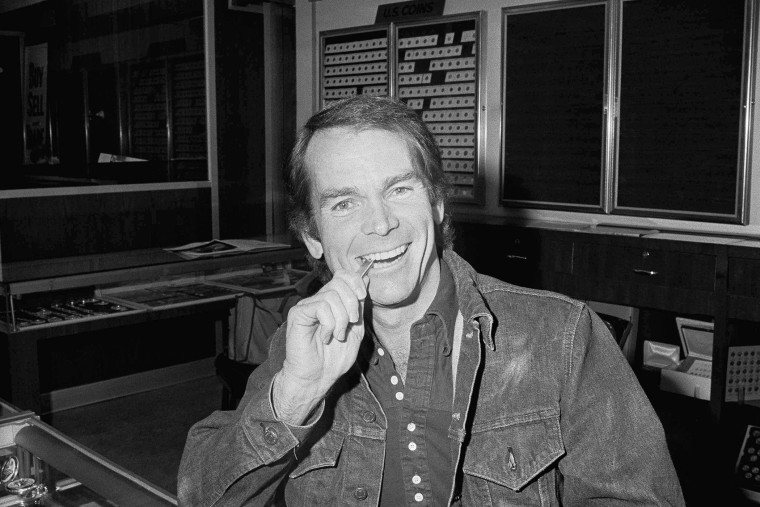 Actor Dean Jones bites a two-ounce bar he bought in Los Angeles, one second after the purchase became legal, Dec. 31, 1974. (Photo by Harold Filan/AP)