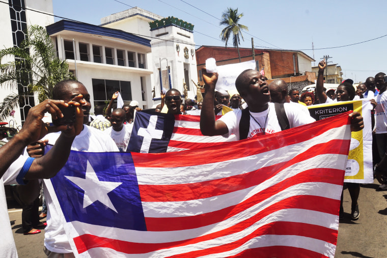 People march with a Liberian flag as they celebrate Liberia being an Ebola free nation in Monrovia, Liberia, Monday, May 11, 2015. (Photo by Abbas Dulleh/AP)