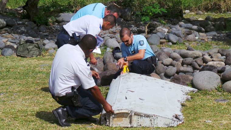 French gendarmes and police inspect a large piece of plane debris which was found on the beach in Saint-Andre, on the French Indian Ocean island of La Reunion, July 29, 2015. (Photo by Prisca Bigot/Zinfos974/Reuters)