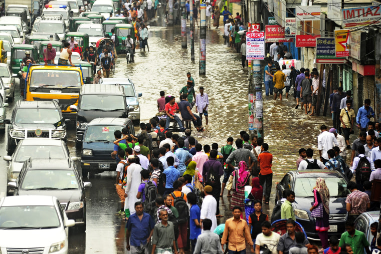 Citizens of Dhaka, Bangladesh are caught in heavy downpour at Kazi Nazrul Islam Avenue on Sept. 1st, 2015. (Photo by Firoz Ahmed/Demotix/Corbis)