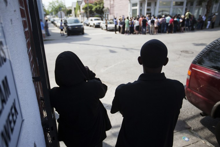 A couple watch from across the street during a news conference outside the Charleston NAACP office regarding the shooting death of Walter Scott by a North Charleston police officer, Thursday, April 9, 2015. (Photo by David Goldman/AP)