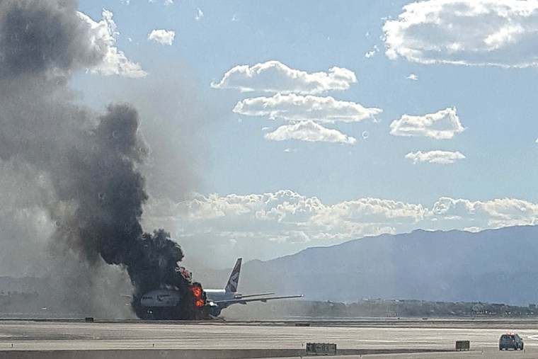 Smoke billows out from a plane that caught fire at McCarren International Airport on Sept. 8, 2015, in Las Vegas, Nev. (Photo by Eric Hays/AP)