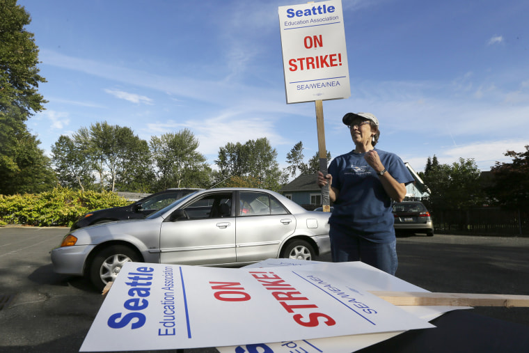Nancy Kiser, a fifth-grade teacher at Kimball Elementary School, examines a picket sign to be used in the event of a strike by teachers in the Seattle School District on Sept. 8, 2015, in Seattle, Wash. (Photo by Ted S. Warren/AP)