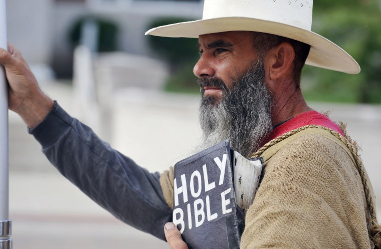 Allan Hoyle, of North Carolina, stands with bible in hand in support of Kim Davis at the Rowan County Judicial Center, Sep. 9, 2015. (Photo by Chris Tilley/Reuters)