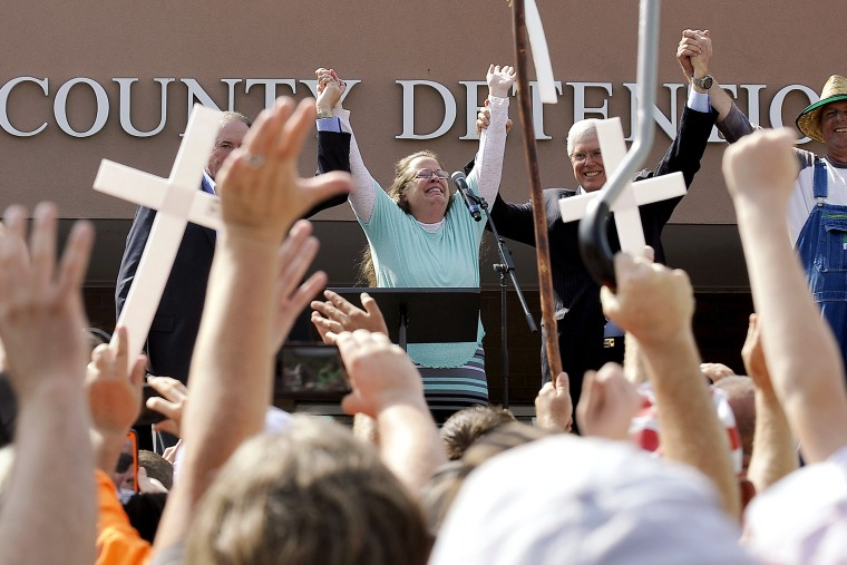 Kim Davis, flanked by Mike Huckabee, her attorney and her husband, celebrates after her release from the Carter County Detention center in Grayson, Ky., Sept. 8, 2015. (Photo by Chris Tilley/Reuters)