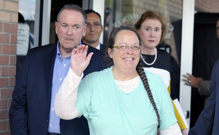 Kim Davis, flanked by Republic presidential candidate Mike Huckabee waves as she walks out of jail, Sep. 8, 2015. (Photo by Chris Tilley/Reuters)
