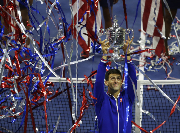 Novak Djokovic, of Serbia, holds up the championship trophy after defeating Roger Federer, of Switzerland, in the men's championship match of the U.S. Open tennis tournament, Sep. 13, 2015, in New York. (Photo by Seth Wenig/AP)
