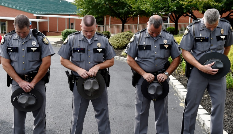 Kentucky State Troopers, from left, Eric Dilback, Lonnie Bell, Chris McKee, and Sean McKinney bow in prayer during a road renaming ceremony in memory of Chase Trent in Zion, Ky., Aug. 29, 2015. (Photo by Darrin Phegley/The Gleane/AP)