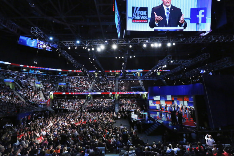Republican presidential candidate Wisconsin Gov. Scott Walker appears on the screen hanging above the debate at the Quicken Loans Arena August 6, 2015 in Cleveland, Ohio. (Photo by Chip Somodevilla/Getty)