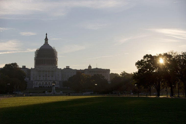 The sun rises behind the U.S. Capitol Building grounds in Washington, D.C., Oct. 20, 2014. (Photo by Carolyn Kaster/AP)