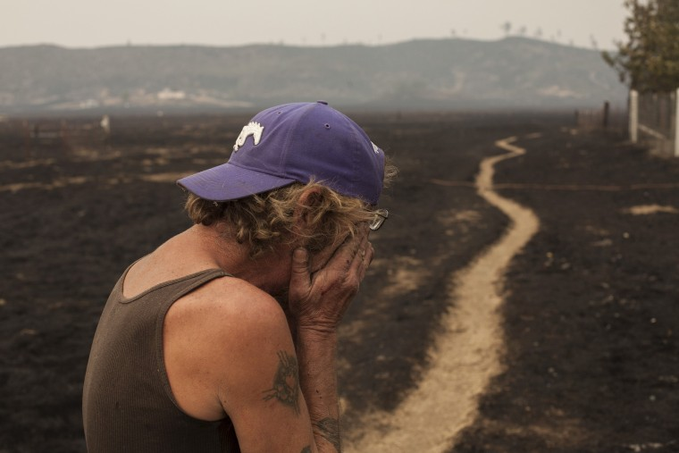 Robert Hooper, exhausted after several days with little sleep, is overcome with emotion while surveying what's left of his property near Middleton, Calif. Sept. 14, 2015. (Photo by David Ryder/Reuters)