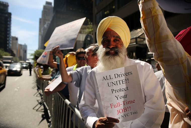 New York City taxi drivers hold a rally in front of Governor Andrew Cuomo's office to protest against recent inroads made by the Uber car service on Sept. 16, 2015 in New York City. (Photo by Spencer Platt/Getty)