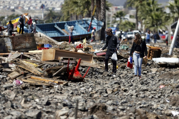 People walk through debris left behind by an earthquake-triggered tsunami in the coastal town of Coquimbo, Chile on Sept. 17, 2015. (Photo by Luis Hidalgo/AP)