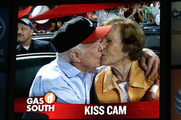 """Former President Jimmy Carter kisses his wife, Rosalynn, on the """"Kiss Cam"""" during a baseball game between the Atlanta Braves and the Toronto Blue Jays, Sept. 17, 2015, in Atlanta. (Photo by John Bazemore/AP)"""