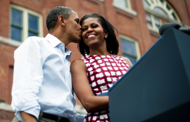 President Barack Obama (L) kisses First Lady Michelle Obama (R) as they arrive to deliver remarks during a campaign event in Dubuque, Iowa, on Aug. 15, 2012, during his three-day campaign bus tour across the state. (Photo by Jim Watson/AFP/Getty)