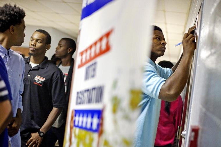 Students at Clark Atlanta University fill out voter registration forms, Sept. 18, 2012, in Atlanta, Ga. (Photo by David Goldman/AP)