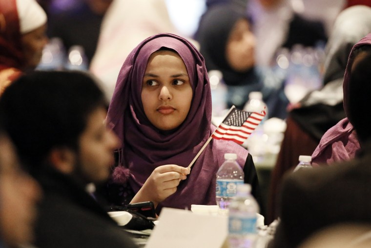 A young woman waves an American flag along with others at the beginning of a Muslim conference against terror and hate at the Curtis Culwell Center, Saturday, Jan. 17, 2015, in Garland, Tex. (Photo by Tony Gutierrez/AP)