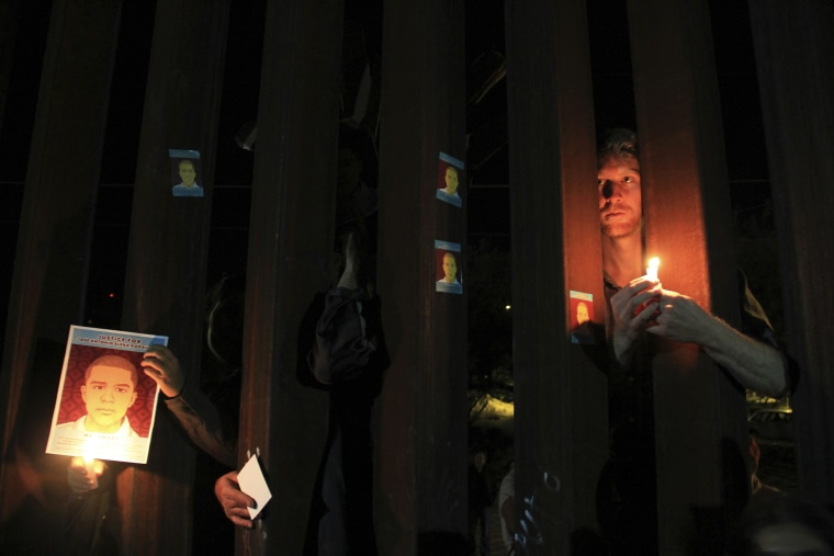 Activists hold candles and pictures of late Mexican youth Jose Antonio Elena Rodriguez through the border fence between Mexico and the U.S. in Nogales, Oct. 10, 2013. (Photo by Stringer/Reuters)
