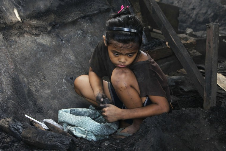 A girl collects pieces of charcoal for sale at a market, in Manila, the Philippines, March 2, 2012. (Photo by Romeo Ranoco/Reuters)