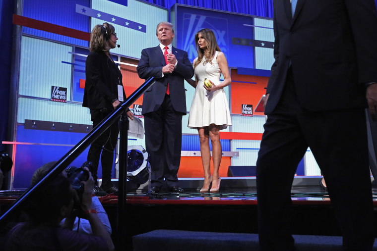Republican presidential candidate Donald Trump (C) and his wife Melania Trump stand on the stage after the first prime-time presidential debate on Aug. 6, 2015 in Cleveland, Ohio. (Photo by Chip Somodevilla/Getty)