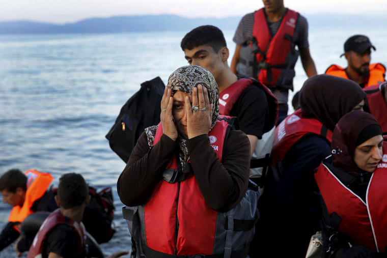 A Syrian refugee reacts while travelling in an overcrowded dinghy as it arrives at a beach on the Greek island of Lesbos, after crossing part of the Aegean Sea from Turkey, Sept. 25, 2015. (Photo by Yannis Behrakis/Reuters)