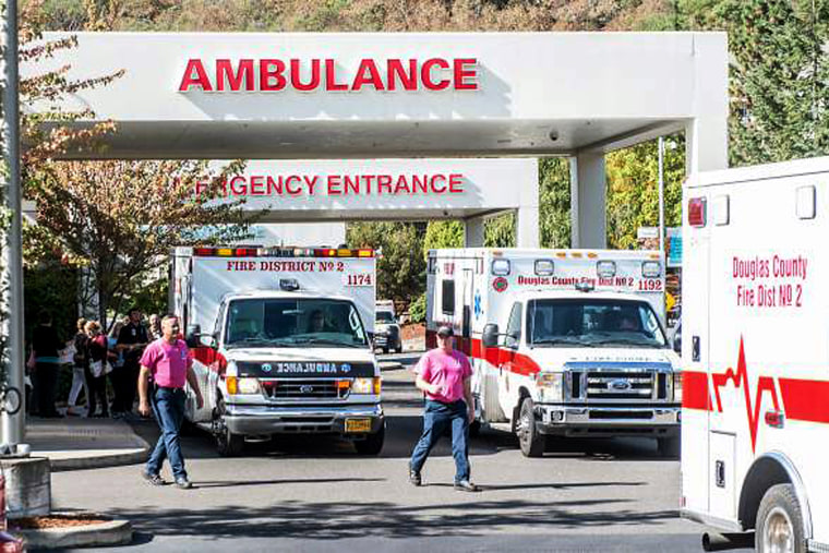 Paramedics return to their ambulances after delivering patients to Mercy Medical Center in Roseburg, Ore., following a deadly shooting at Umpqua Community College, in Roseburg, Oct. 1, 2015. (Photo by Aaron Yost/Roseburg News-Review/AP)