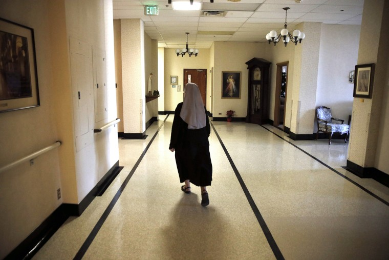 A nun walks in the hallway at the Mullen Home for the Aged, run by Little Sisters of the Poor, in Denver, Colo. (Photo by Brennan Linsley/AP)