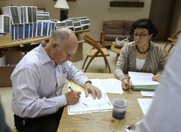California Gov. Jerry Brown signs one of the hundreds of bills he has left to deal with as Garciela Castillo-Krings, his deputy legislative secretary, looks on at his Capitol office in Sacramento, Calif., Oct. 9, 2015. (Photo by Rich Pedroncelli/AP)