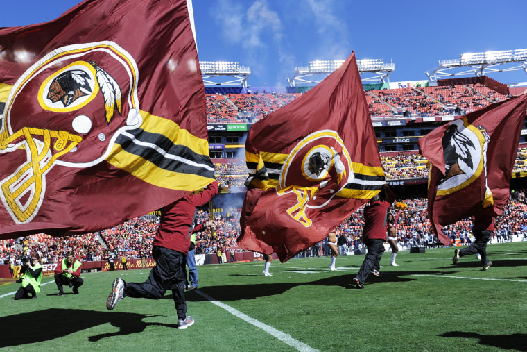 The flag crew runs onto the field before the game between the Washington Redskins and the Tennessee Titans at FedEx Field on Oct. 19, 2014. (Photo by Toni L. Sandys/The Washington Post/Getty)