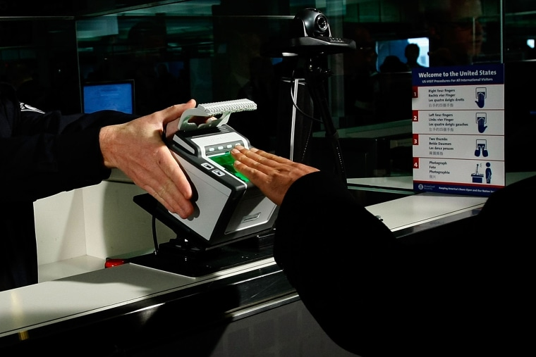 International airline passengers are fingerprinted on all ten fingers by a U.S. Customs and Border Protection officer on arrival at Dulles International Airport, Dec. 10, 2007 in Sterling, Va. (Photo by Win McNamee/Getty)
