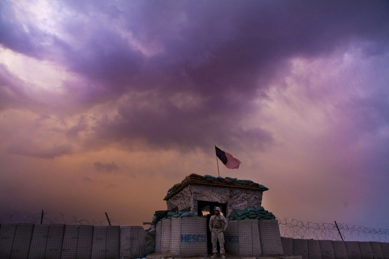 A U.S. Marine from the First Battalion Eighth Marines Alpha Company looks out as an evening storm gathers above an outpost near Kunjak in southern Afghanistan's Helmand province, Feb. 22, 2011. (Photo by Finbarr O'Reilly/Reuters)