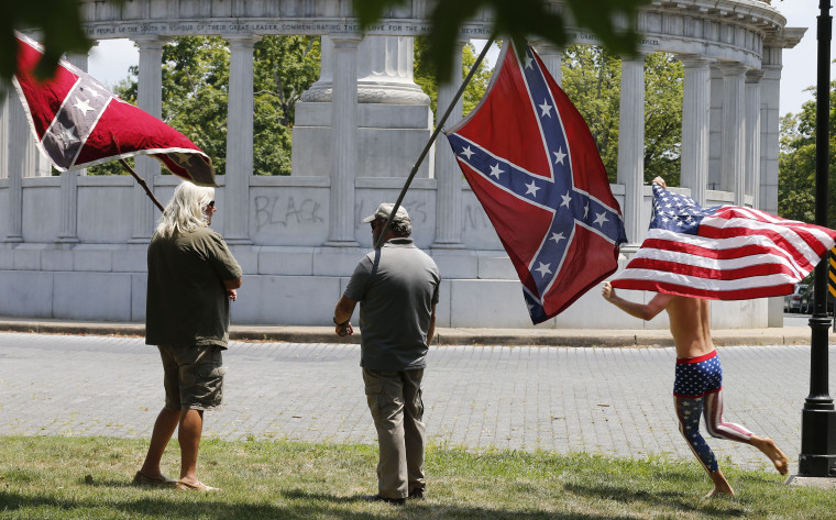 Members of the Virginia Flaggers demonstrate near the monument for Confederacy President Jefferson Davis as a runner carries an American flag, June 25, 2015, on Monument Avenue in Richmond, Va. (Photo by Steve Helber/AP)