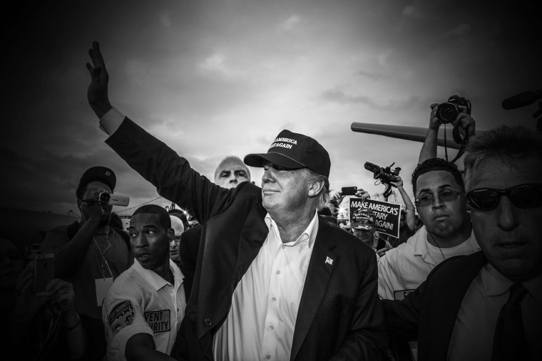 """Republican presidential candidate Donald Trump waves to the crowd at his """"Make America's Military Great Again"""" rally, which was held aboard the retired USS Iowa battleship, in Los Angeles, Calif., on Sept. 15, 2015.(Photo by Mark Peterson/Redux for MSNBC)"""