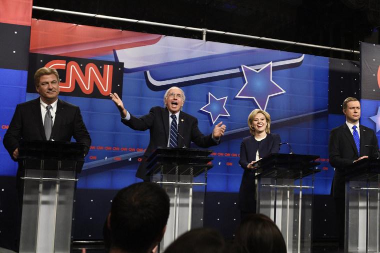 "Alec Baldwin as Jim Webb, Larry David as Bernie Sanders, Kate McKinnon as Hillary Clinton, Taran Killam as Martin O'Malley during the ""Democratic Debate Cold Open"" sketch on Oct. 17, 2015. (Photo by Dana Edelson/NBC/NBCU Photo Bank/Getty)"