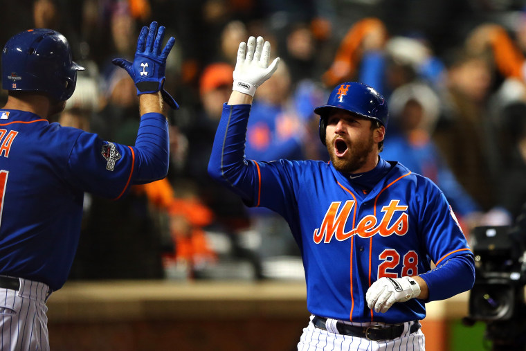Daniel Murphy #28 of the New York Mets celebrates with his teammates after hitting a two run home run in the first inning against Jake Arrieta #49 of the Chicago Cubs during game two. (Photo by Elsa/Getty)