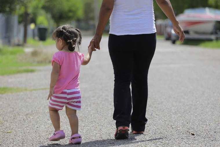 A woman who is in the country illegally walks with her two-year-old daughter who was born in the in the United States but was denied a birth certificate, Sullivan City, Texas, Sep. 16, 2015. (Photo by Eric Gay/AP)