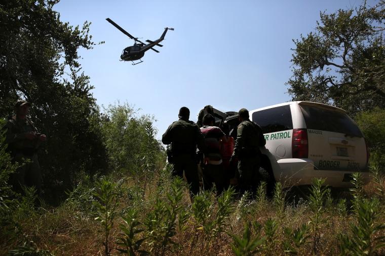 U.S. Border Patrol agents detain undocumented immigrants north of the U.S.-Mexico border on Aug. 6, 2015 near Falfurrias, Texas. (Photo by John Moore/Getty)